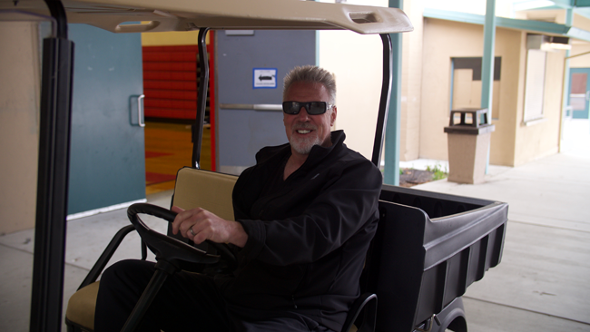 Executive Director of The Wave Program, Darryl Smith, sits in a golf cart after making the rounds during summer camp at PGHS